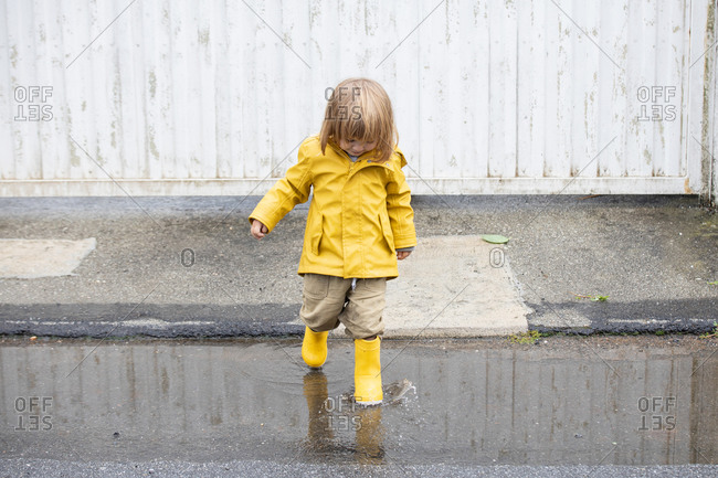 Little playful kid in yellow raincoat and rubber boots walking in puddle and splashing water while having fun after rain