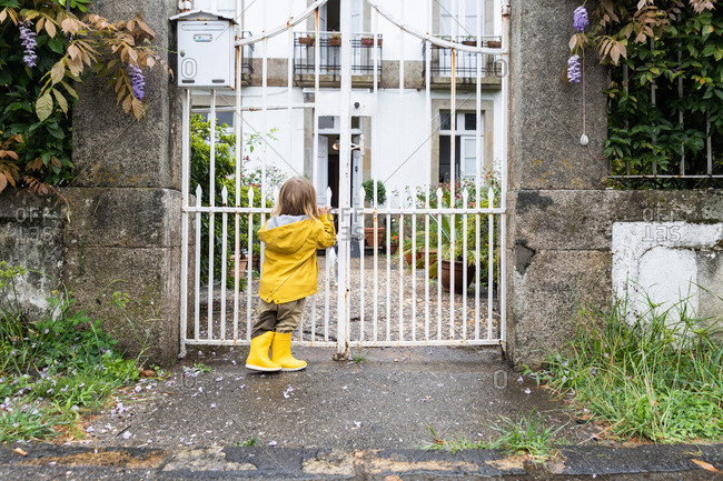 Back view of curious little kid in yellow raincoat standing near metal gates on wet street