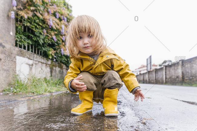Low angle of adorable little child in yellow raincoat playing in puddle and splashing water while entertaining after rain on street looking at camera