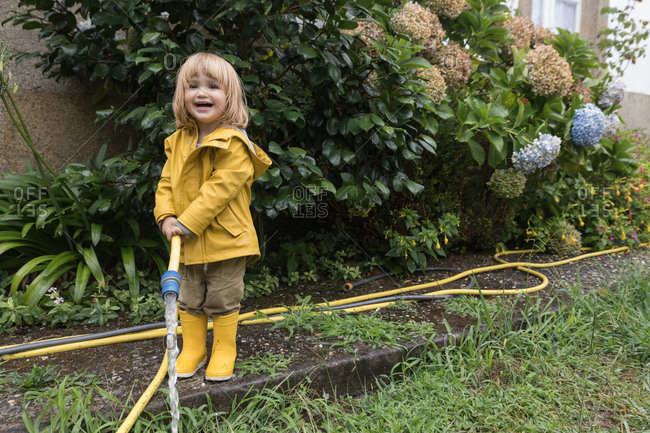 Cute little child wearing yellow raincoat and rubber boots watering garden from hose after rain and looking at camera