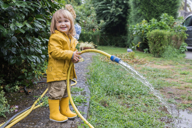 Side view of cute little child wearing yellow raincoat and rubber boots watering garden from hose after rain and looking at camera