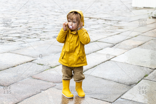 Full body of cute little kid wearing bright yellow raincoat and rubber boots standing on wet pavement and looking away