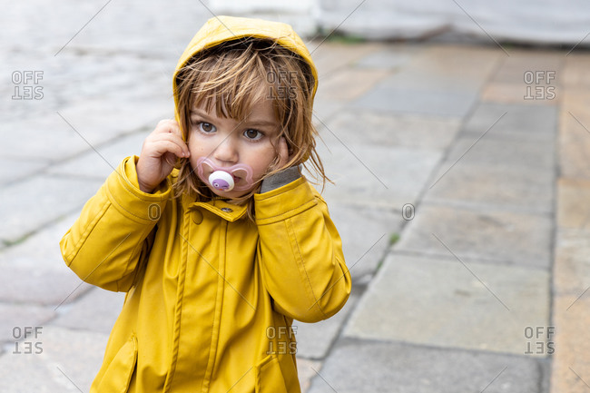 Cute little kid wearing bright yellow raincoat and rubber boots standing on wet pavement and looking away