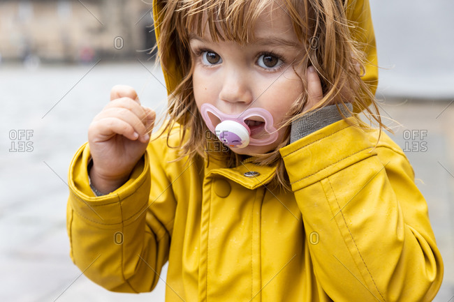 Cute little kid wearing bright yellow raincoat and rubber boots standing on wet pavement and looking at camera