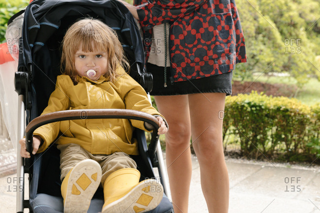 Crop mother standing near baby carriage with upset little kid in yellow raincoat and rubber boots looking at camera