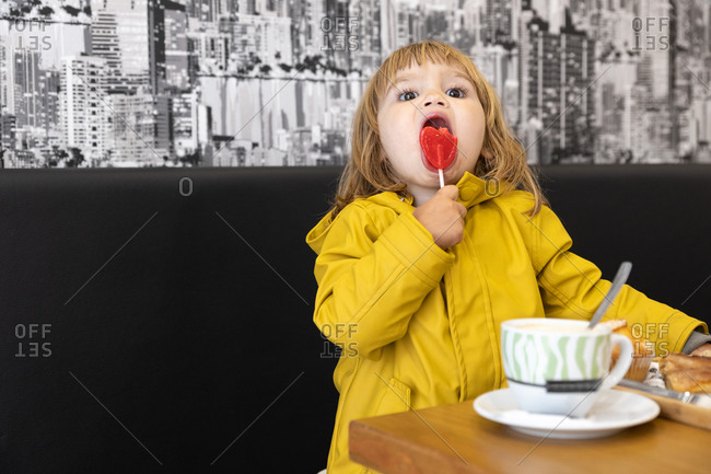Cute little child in yellow raincoat sitting in cafe and eating sweet lollipop looking away