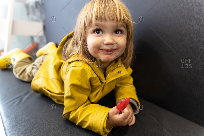 Adorable little kid in yellow raincoat and with dirty mouth lying on sofa in cafe with lollipop and looking away