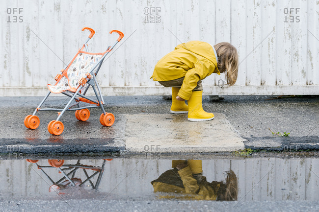 Side view of unrecognizable little kid wearing yellow vivid raincoat and rubber boots having fun on wet asphalt road in city