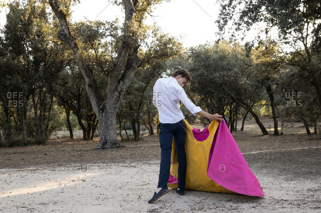 Back view of graceful male matador practicing on meadow with yellow and pink cloak on sunny day