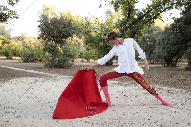 Side view of slim male bullfighter in red pants and white shirt holding cloak performing gracefully before corrida in nature