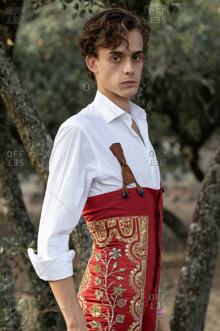 Side view of slender male matador wearing white shirt and red costume decorated with golden sequins standing in nature and looking at camera