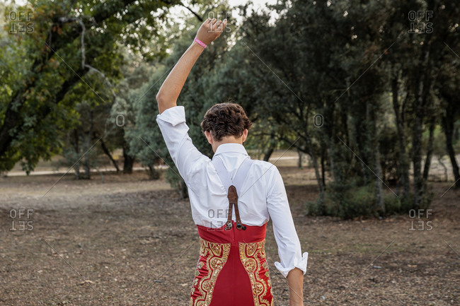 Back view of unrecognizable young male matador wearing white shirt and red costume performing in nature with raised arm before corrida