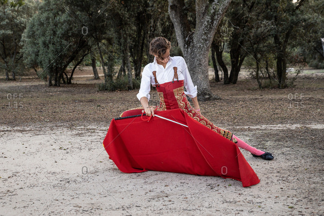 Slim focused male bullfighter in red pants and white shirt holding cloak performing gracefully before corrida in nature