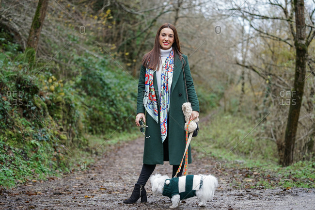 Delighted female wearing coat and boots standing on path with white fluffy dog on leash during stroll in park in fall and looking at camera