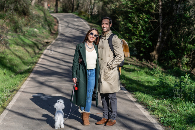 Cheerful couple in outerwear hugging and looking at camera while standing with cute dog in autumn park during stroll on sunny day