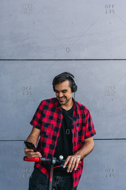 Young smiling stylish ethnic male in headphones surfing internet on cellphone while standing on electric scooter near tiled wall