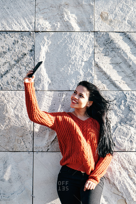 Happy ethnic woman taking selfie while standing against stone wall outdoors on a sunny day