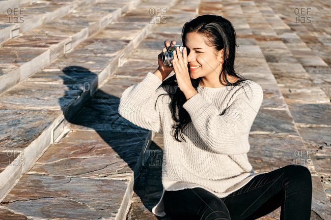 Optimistic ethnic female using photo camera to take pictures of street while sitting on marble stairs