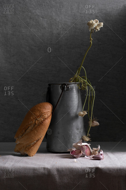 Rustic composition of metal jar with weathered flowers and piece of white bread on table