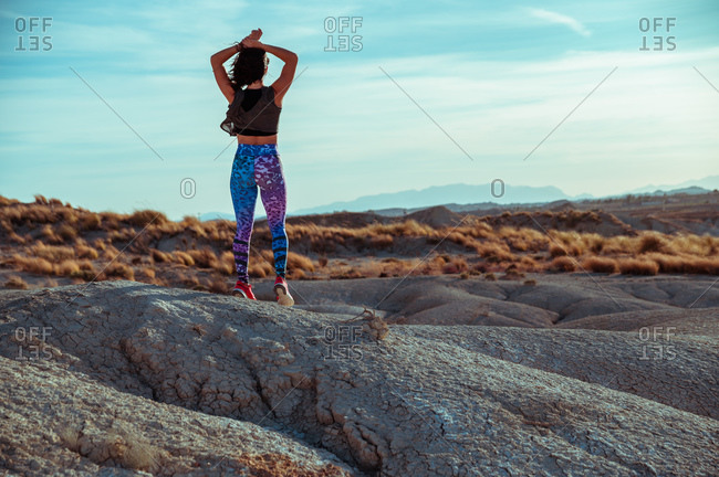 Back view of unrecognizable female in sportswear standing with outstretched arms on rocky hill among desert badlands against blue cloudy sky