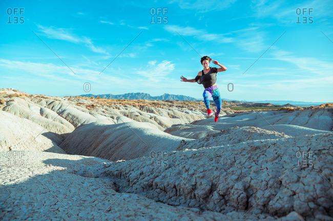 Full body active female athlete in sportswear running and jumping over rocky slope of rough desert hilly terrain under blue sky
