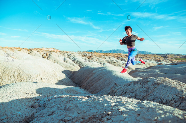 Full body side view of active female athlete in sportswear running and jumping over rocky slope of rough desert hilly terrain under blue sky