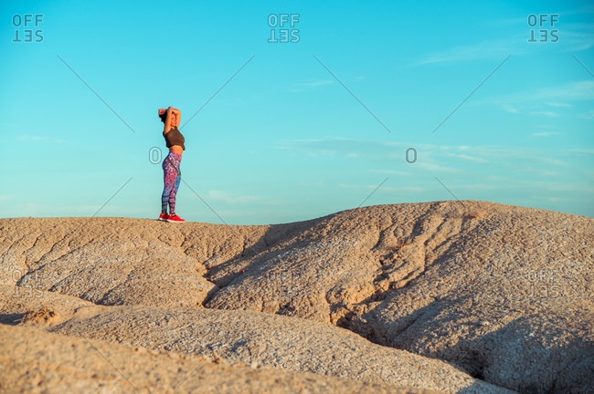 Side view of unrecognizable female in sportswear standing with outstretched arms on rocky hill among desert badlands against blue cloudy sky