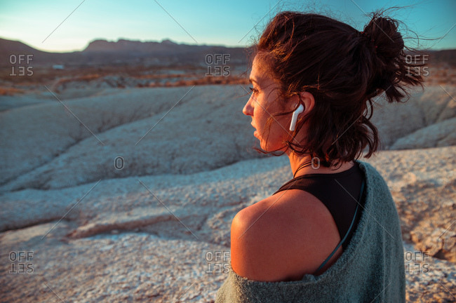 Side view of young female in sportive outfit and listening to music with wireless earbuds contemplating amazing scenery of rough stony badlands at sunset time