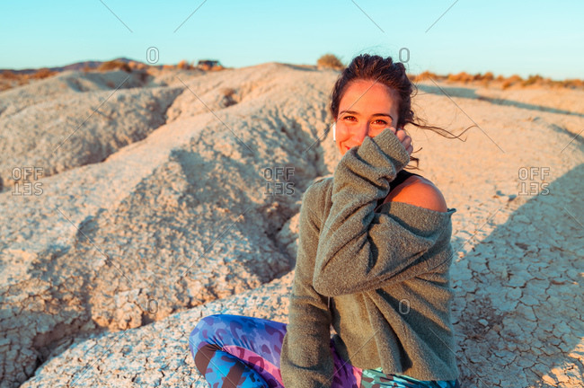 Young female in sportive outfit and listening to music with wireless earbuds contemplating amazing scenery of rough stony badlands at sunset time