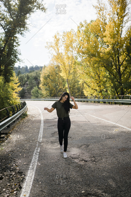 Full body of optimistic young female in casual outfit having fun and dancing on empty asphalt roadway while spending sunny autumn day in countryside