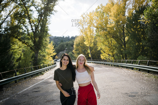 Cheerful young girlfriends in casual clothes embracing and looking at camera while standing on empty asphalt roadway leading through forest in sunny autumn day