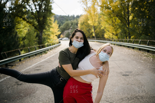 Cheerful young female friends in casual wear and protective masks hugging and having fun while standing on asphalt country road leading through forest in autumn day