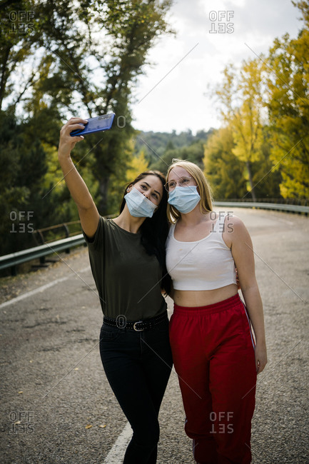 Cheerful young female friends in casual outfits and protective masks taking selfie on smartphone while standing on asphalt road passing through forest in autumn day in countryside