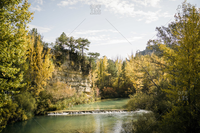 Scenic view of small river with waterfall flowing through mountainous terrain covered with colorful forest in sunny autumn day
