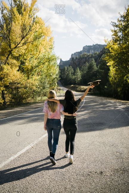 Back view young girlfriends in casual clothes embracing and looking away while standing on empty asphalt roadway leading through forest in sunny autumn day