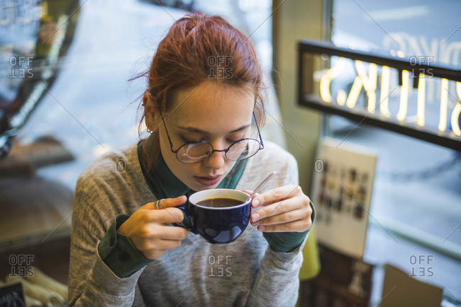 High angle of stylish female sitting at table in cozy cafe and drinking aromatic hot beverage at weekend