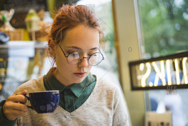 Stylish female sitting at table in cozy cafe and drinking aromatic hot beverage at weekend