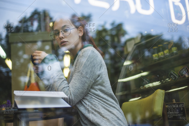 Through glass side view of relaxed female in casual outfit sitting at table with opened book in cozy coffee shop and enjoying aromatic beverage while looking at camera