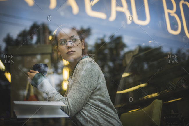 Through glass side view of relaxed female in casual outfit sitting at table with opened book in cozy coffee shop and enjoying aromatic beverage while looking away