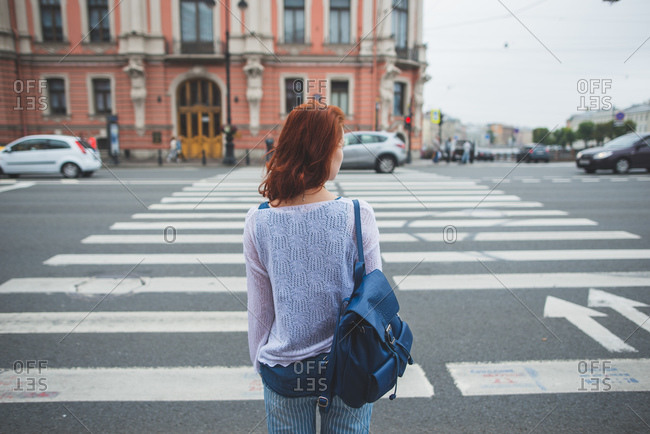 Back view of anonymous female with red hair standing near crosswalk in Saint Petersburg and looking away