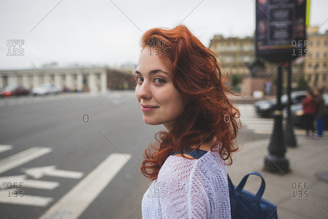 Side view female with red hair standing near crosswalk in Saint Petersburg and looking at camera