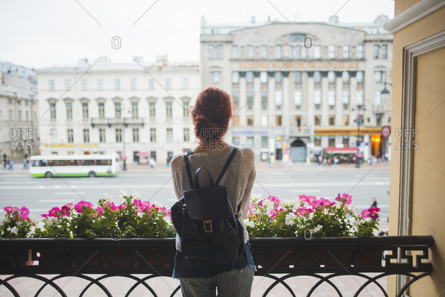 Back view of unrecognizable red haired female tourist with backpack standing alone on terrace of urban building and exploring city view while visiting Saint Petersburg during summer holidays