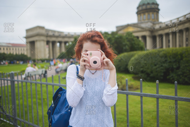 Young red haired female tourist with backpack shooting photo with instant camera while standing against famous Kazan Cathedral in summer day in Saint Petersburg