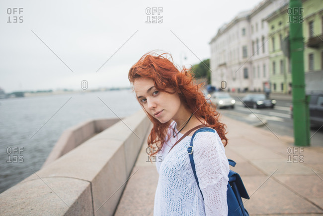 Side view of red haired female tourist with backpack standing near stone fence against river and enjoying wind while resting during sightseeing in cloudy day in Saint Petersburg in Russia