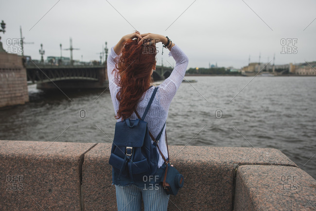 Back view of unrecognizable red haired female tourist with backpack standing near stone fence against river and enjoying wind while resting during sightseeing in cloudy day in Saint Petersburg in Russia