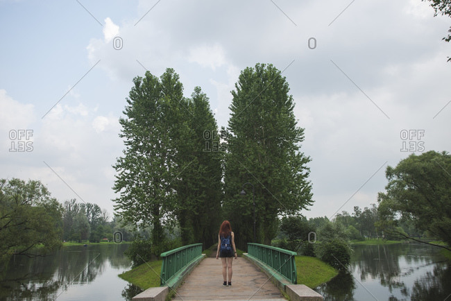 Full body back view of unrecognizable female traveler standing on old footbridge crossing river and leading to small green island while exploring Saint Petersburg neighborhoods in summer day