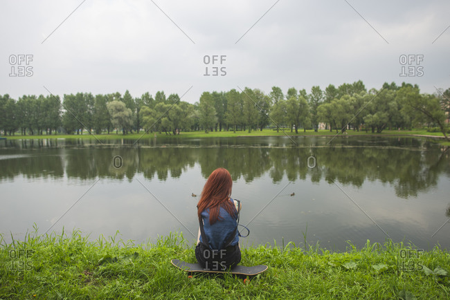 Back view of unrecognizable red haired young female with backpack sitting on skateboard on green grassy shore of calm lake while spending summer day in park