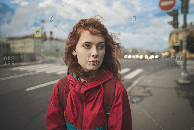 Serious millennial redhead female with curly hair wearing red jacket looking away while standing alone against road and historic buildings in windy day in Saint Petersburg in Russia