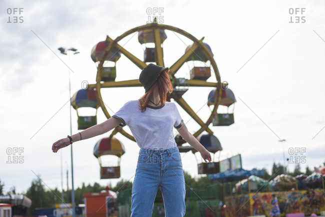 Low angle of carefree young red haired female teenager in trendy hat and jeans enjoying summer day in amusement park while standing against Ferris wheel