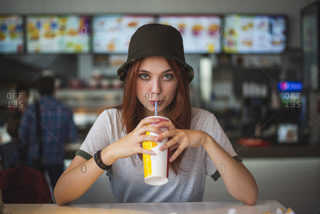 Happy teen female in trendy hat with cup of takeaway cold drink with straw in hands resting at counter in modern cafeteria